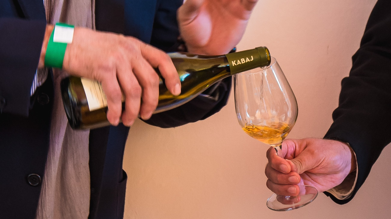 orange wine being poured into a glass