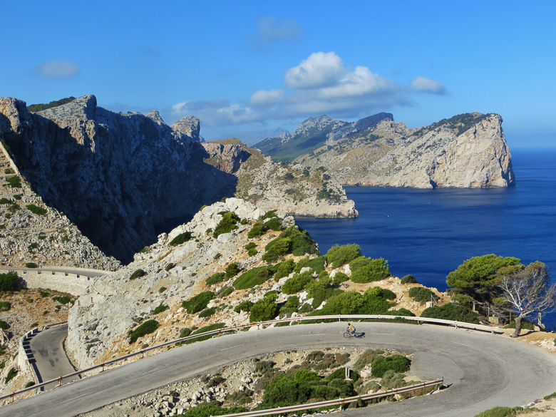 Winding road with cyclist in Mallorca, Spain
