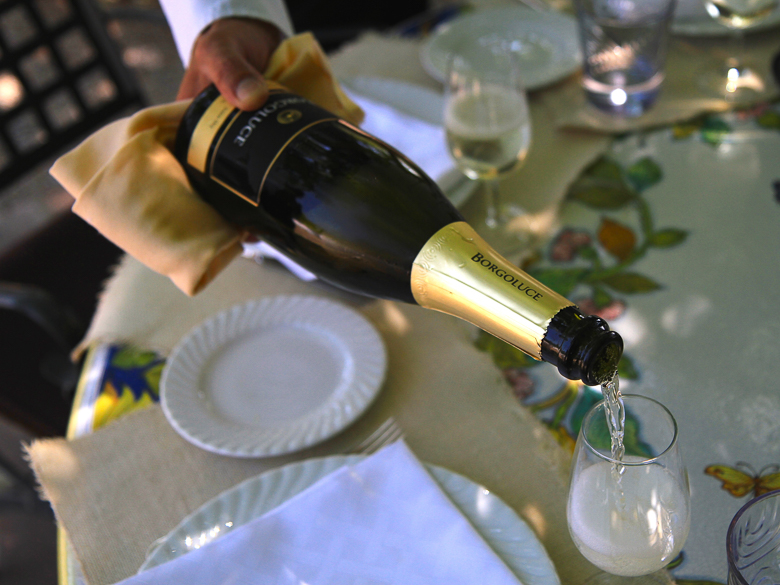 A bottle of champagne is poured at a table