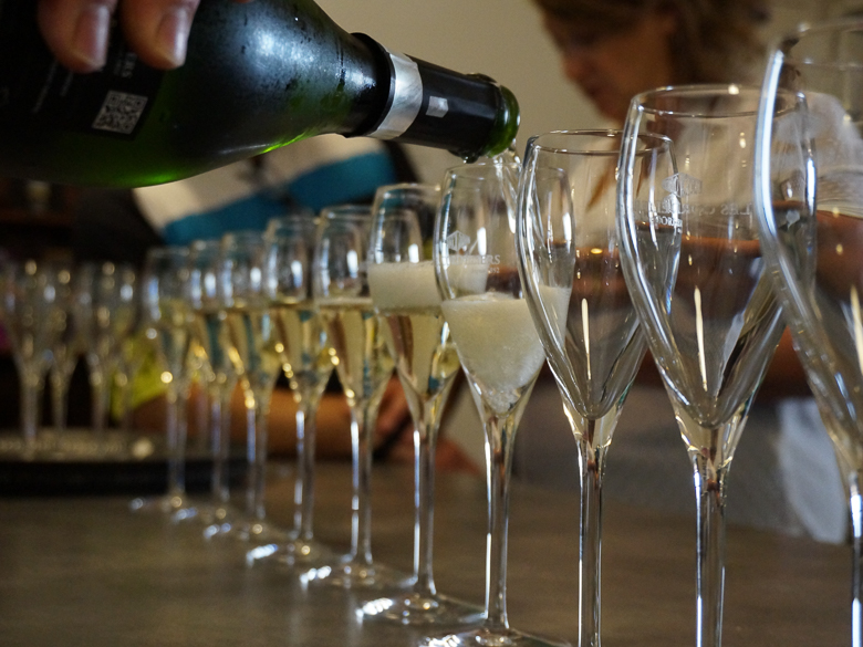 A row of champagne flutes being filled
