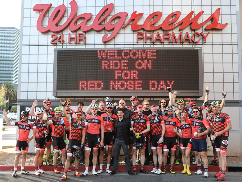 Riders for Red Nose Day stand in front of a Walgreens