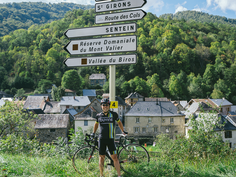 Cyclist standing by road signs in the Pyrenees, France