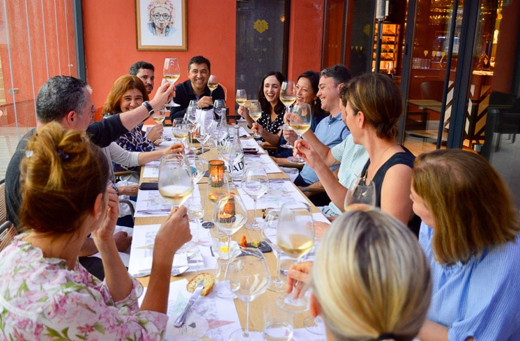 DuVine guests seated around a table, raising their glasses for a toast during dinner in Burgundy, France
