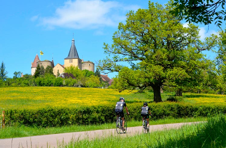 Two people riding bikes on a small road in Burgundy, surrounded by greenery and a castle in the distance
