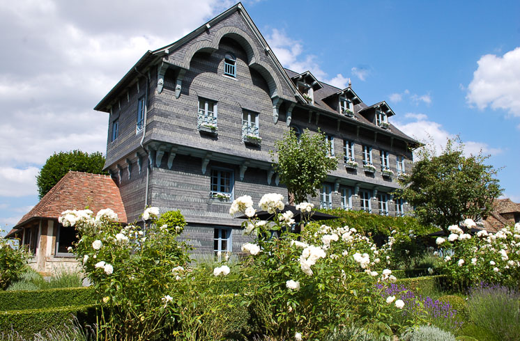 Exterior of 17th-century La Ferme Saint Siméon hotel with white roses growing in foreground