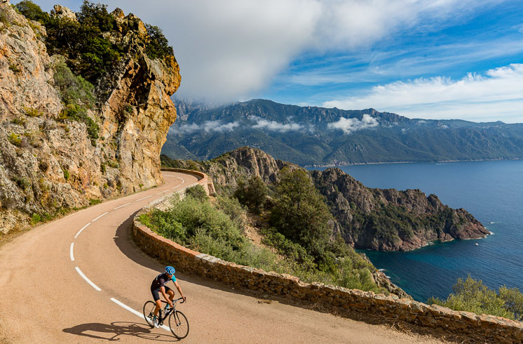 Landscape of mountains and ocean with DuVine cyclist in Corsica, France