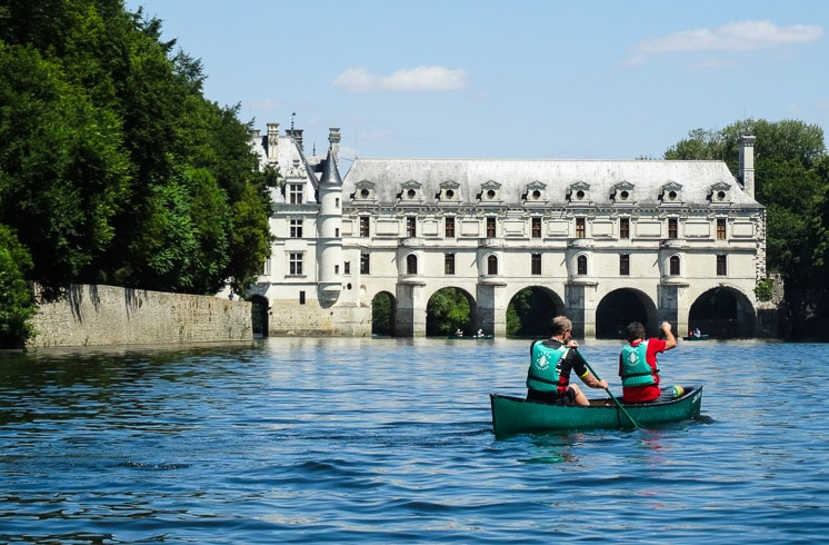 A couple in a canoe prepares to paddle through an arch beneath Château de Chenonceau on DuVine tour in Loire Valley