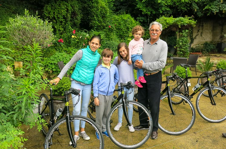 Family with grandparent and young children poses for a smiling photo in front of DuVine bikes in Loire Valley, France