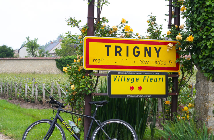 A DuVine bike leans against a yellow sign indicating the village of Tigny,