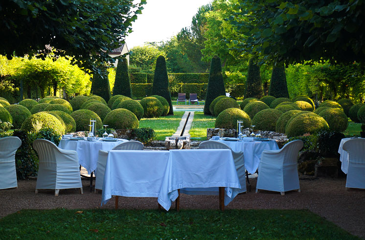 Outdoor tables set for dinner with white tablecloth in a topiary garden at Le Vieux Logis hotel in Trémolat, France