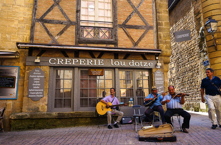 A small group of musicians seated outside Creperie Lou Dotze in Sarlat-la-Canéda