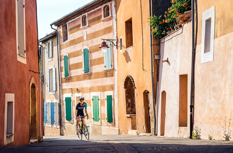 A cyclist riding between red-orange buildings in Rousillon on a DuVine tour of Provence