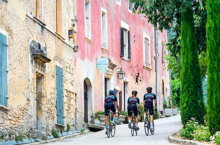 Cyclists pedal uphill on a village road, alongside a pastel pink building in Provence