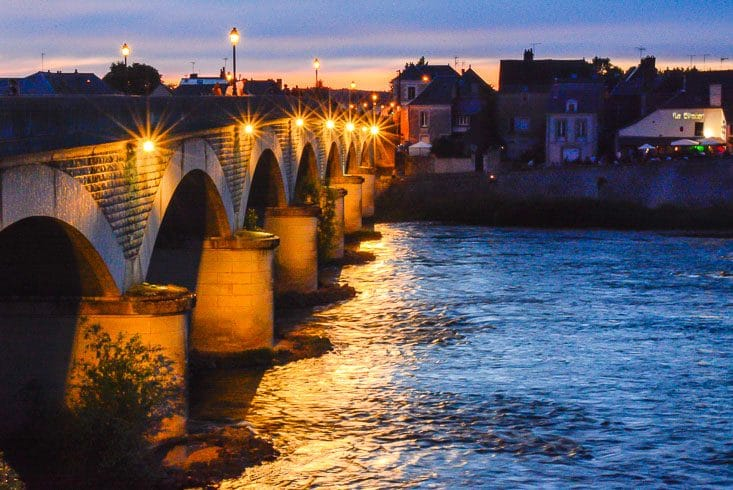 A lighted bridge spans a river at sunset in a village of the Loire Valley, France