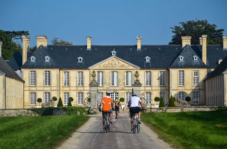 DuVine cyclists seen from behind as they approach Relais & Chateaux hotel Château d'Audrieu in Audrieu, Normandy, France