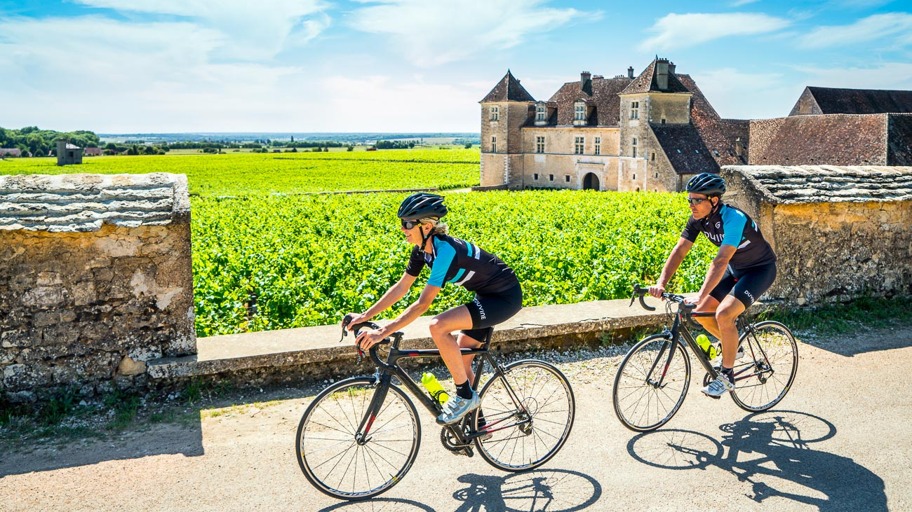 Duo of DuVine cyclists surrounded by bright green vineyards in Bordeaux