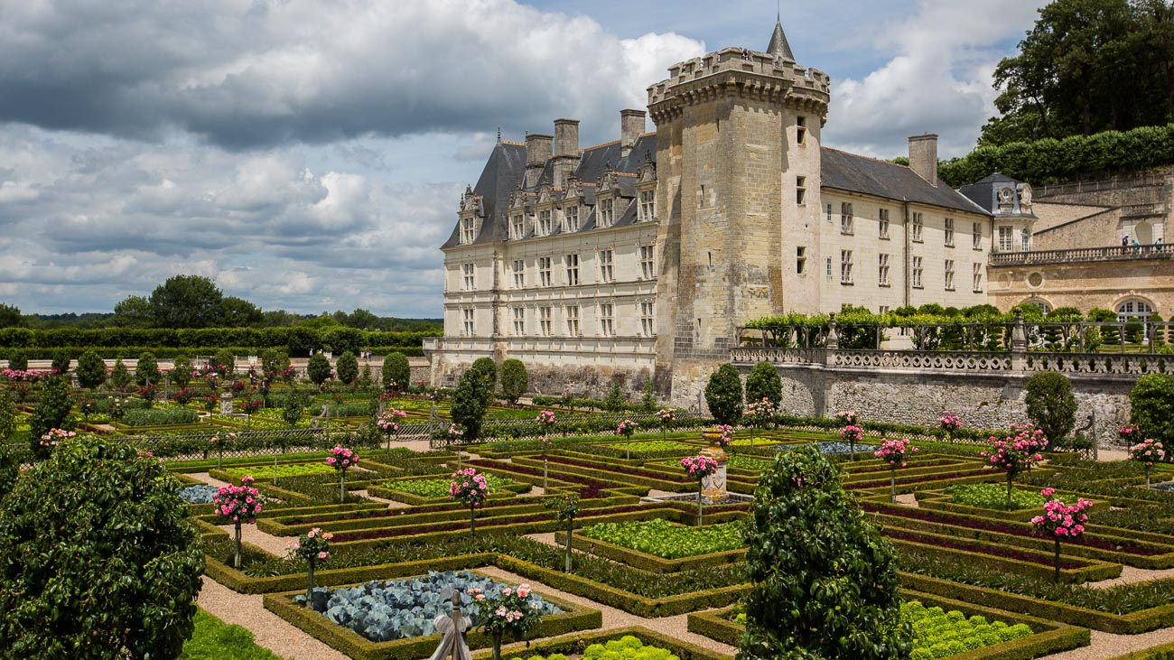 Château de Villandry castle in background with hedge mazes, rosebush topiaries, and vegetable gardens in foreground