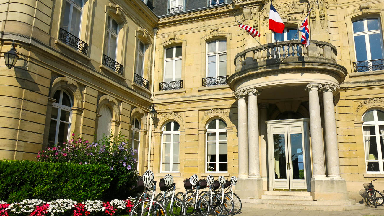 DuVine bikes lined up with helmets resting on handlebars in front of Chateau Les Crayeres hotel