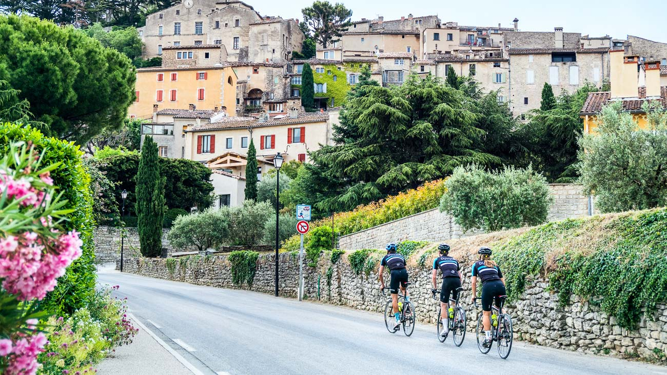 Three Cyclists on DuVine tour of Provence, approaching a village on the road