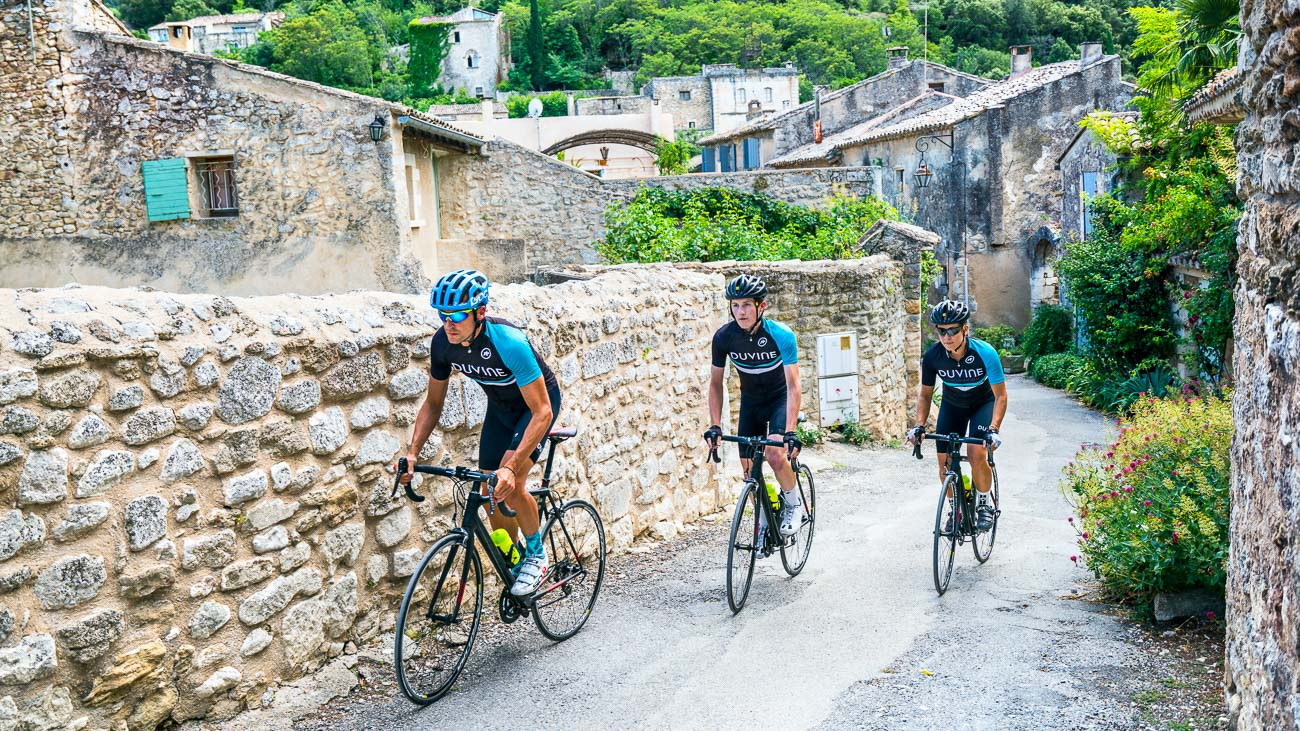 Three DuVine cyclists ride single-file beside a stone wall in a Provencal village