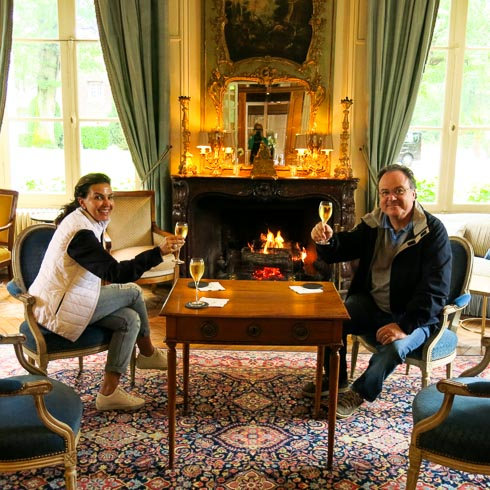 A couple sits in front of a fireplace at Domaine des Hauts de Loire Hotel, toasting with glasses of Champagne