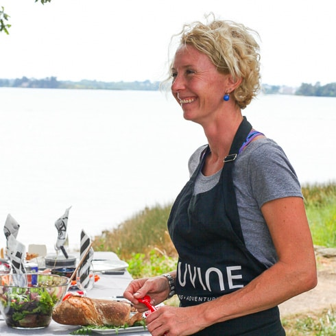 DuVine guide wearing an apron while preparing a picnic by the water in Brittany, France
