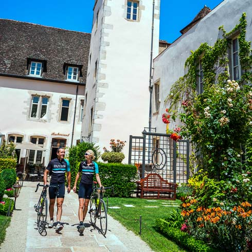Two cyclists walking their bikes in the courtyard of Le Cep hotel in Beaune