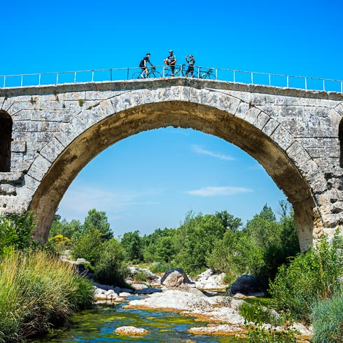 Three cyclists take a break with their bikes on top of the Pont Julien bridge in Bonnieux, France