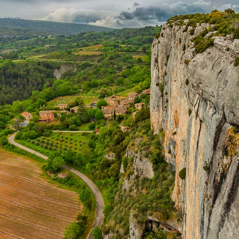A sheer granite cliff and aerial view of a village nestled against it in Provence, France