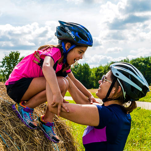 Mother wearing a bike helmet holds her young daughter in a bike helmet atop a bale of hay during DuVine's Loire Valley, France