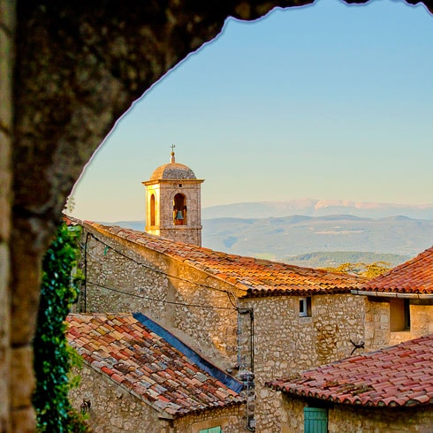 Sunset over a bell tower, seen through a stone archway in a Provencal village
