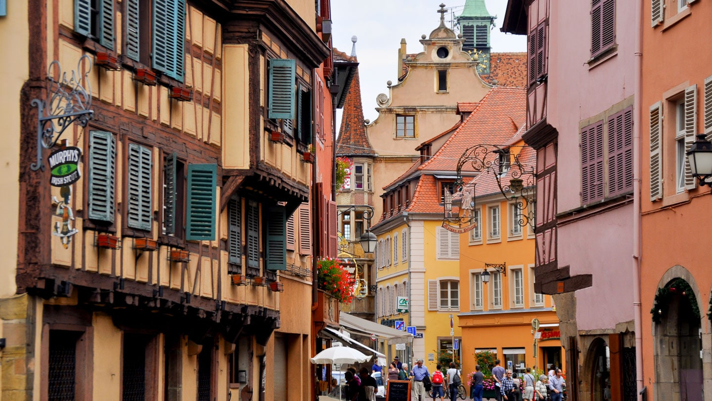 Village with traditional Alsatian architecture and pedestrians in Alsace, France