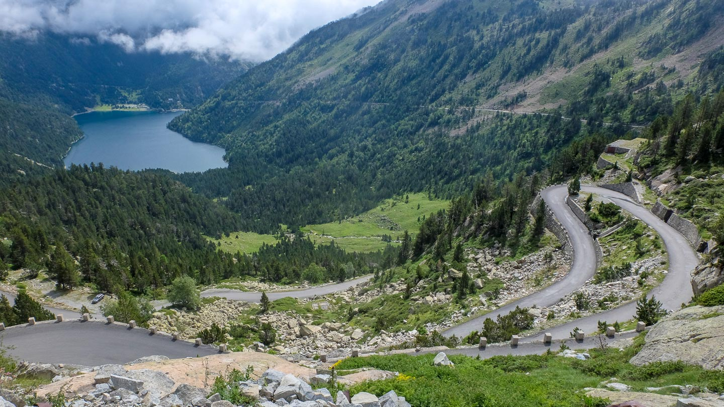 The Col du Peyresourde with a winding road, mountains, forests, and a lake in the distance in the Pyrenees, France