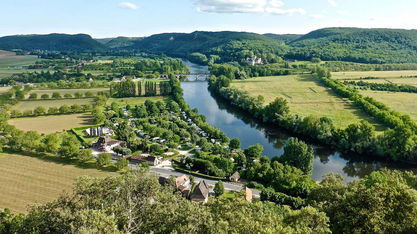 An aerial landscape of green fields and trees bisected by a river in the Dordogne