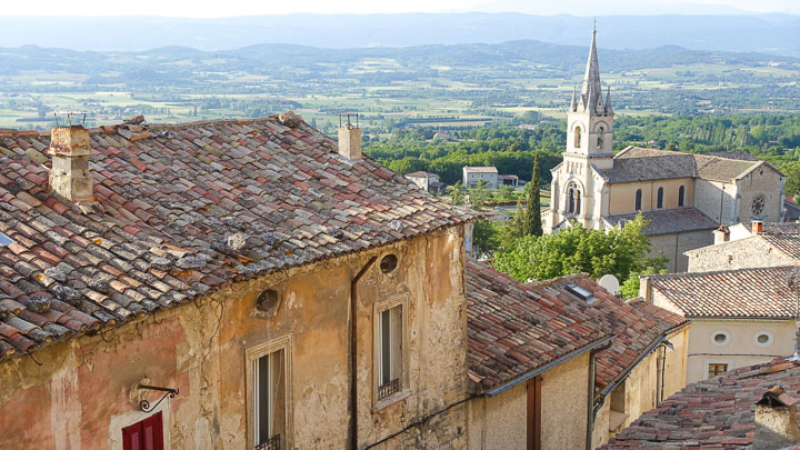 A terracotta rooftop and church in the background in Bonnieux, Provence, France