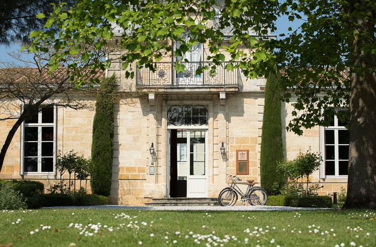 Front garden and main entrance of Château Cordeillan-Bages hotel with bikes