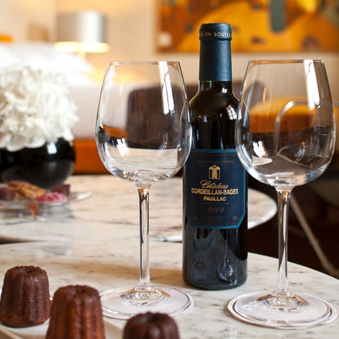 Typical Bordeaux canelé pastry and a bottle of Cordeillan-Bages red wine with glasses