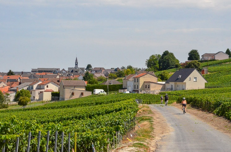 DuVine cyclists riding on a road in Champagne, France with vineyards on one side and a village on the other