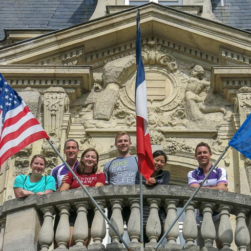 Family on a balcony at Chateau Les Crayeres, looking below and surrounded by French and American flags