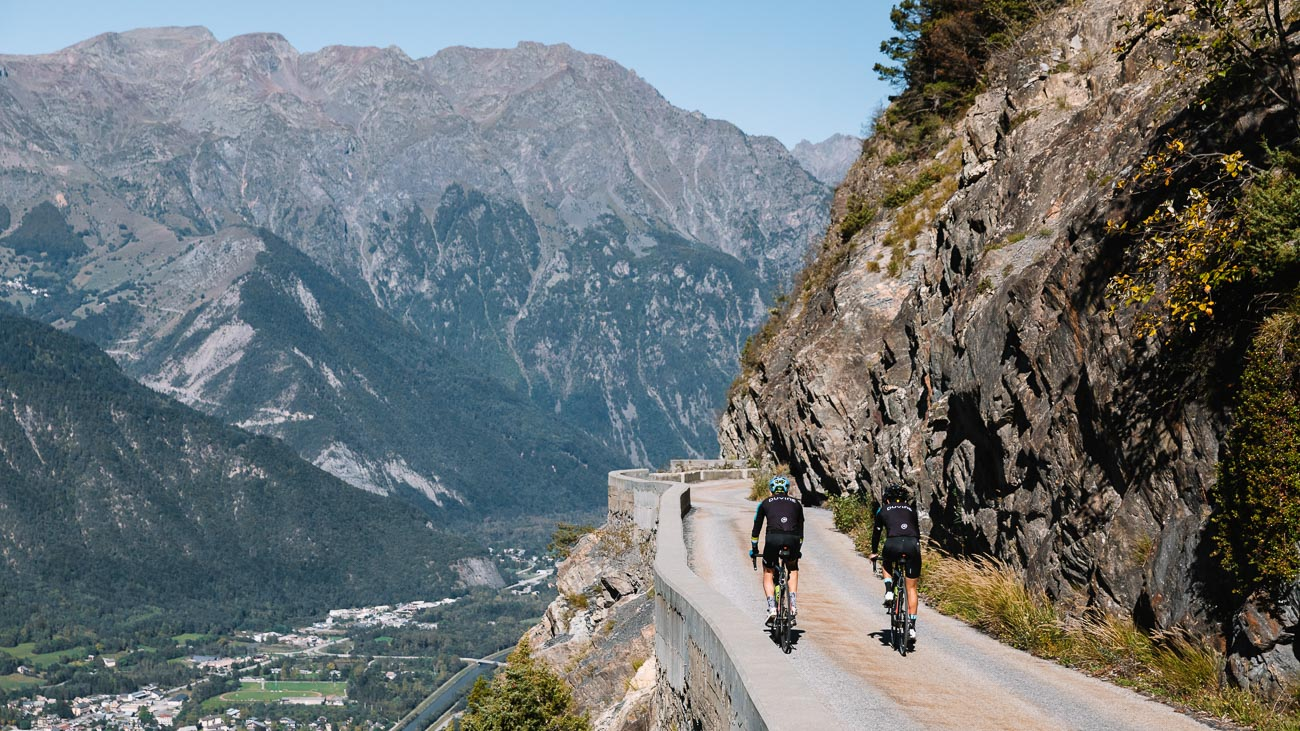 Two cyclists riding on a mountain road in the French Alps