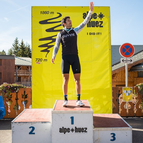 Cyclist posing at the Tour de France podium after completing the Alpe d'Huez ride