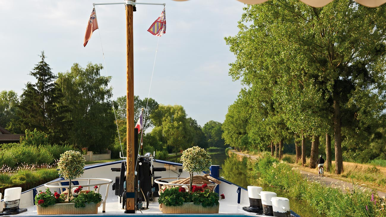 View of the bow and mast of the Belmond Amaryllis river barge as it sails on the Burgundy Canal in France