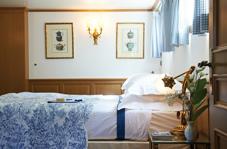 Passenger cabin with bed made up in French blue linens aboard the Belmond Amaryllis