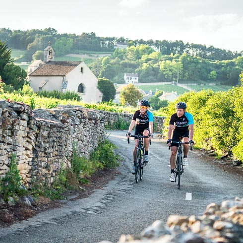Two bikers on a vineyard road in Burgundy, France