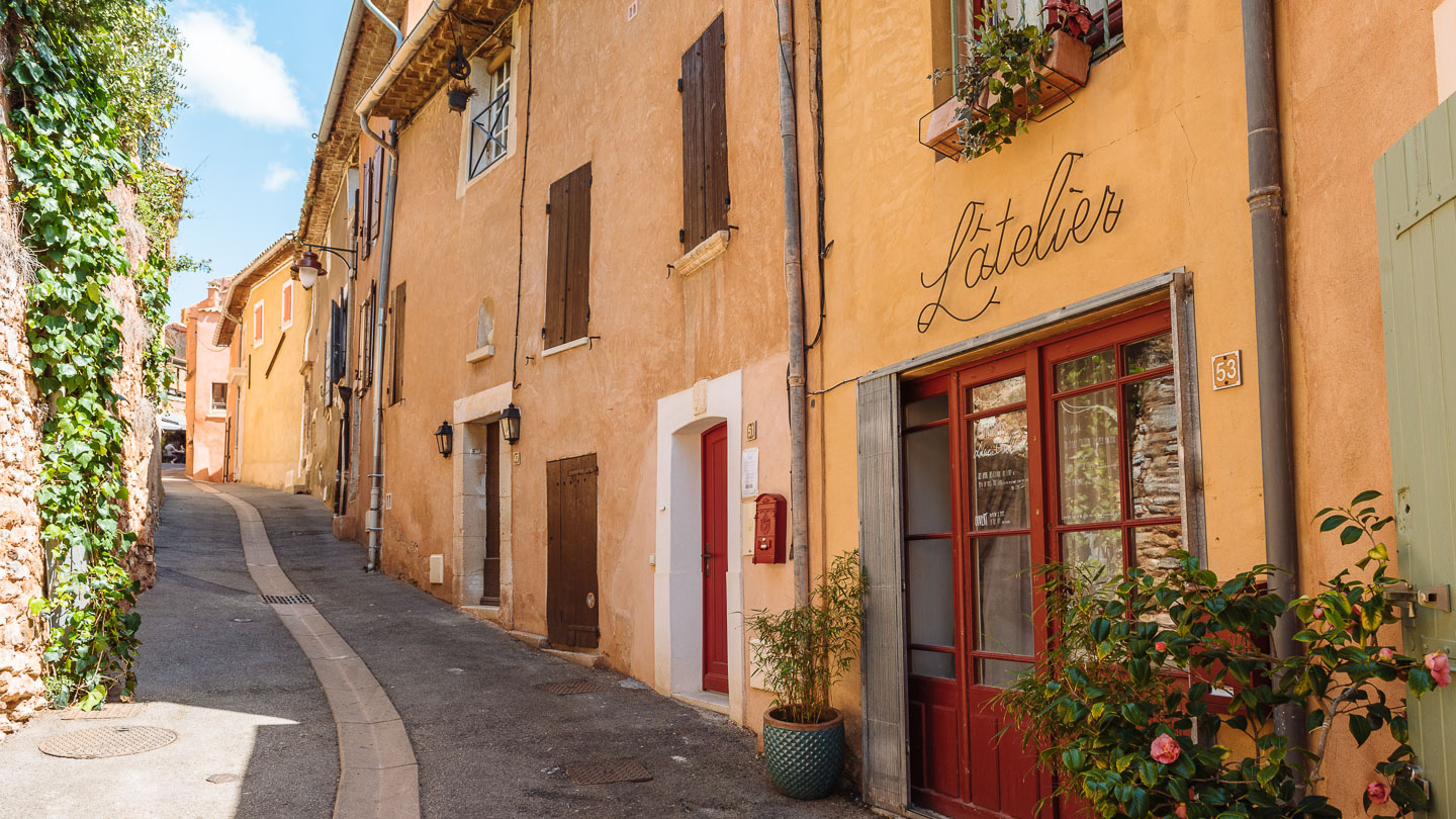 Narrow street in the Provençal village of Rousillon, France, with red-orange buildings