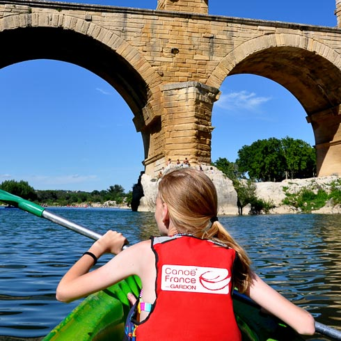 Child wear a life vest while paddling a canoe under a bridge on the Sorgue river in Provence, France
