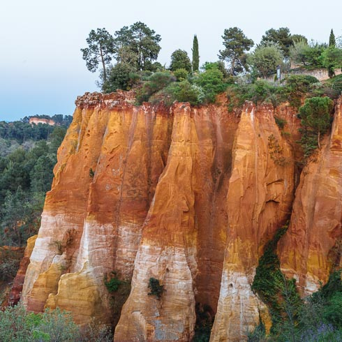 Landscape of red cliffs topped with scrub in Rousillon, Provence, France